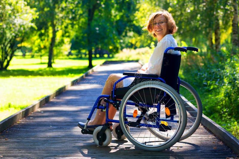Glückliche junge erwachsene Frau auf Rollstuhl im Park stockfoto