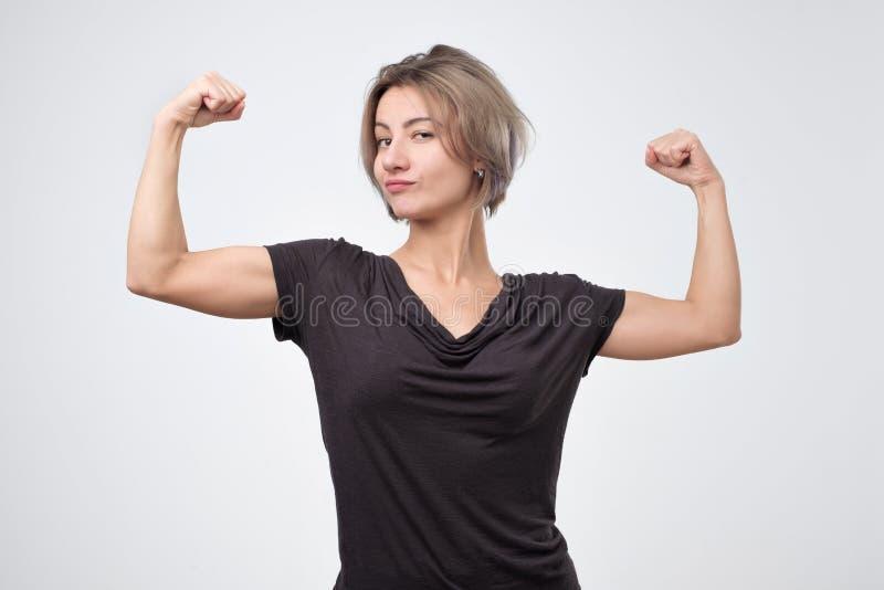 Glückliche junge europäische Frau, die ihre starke Hand zeigt stockbild