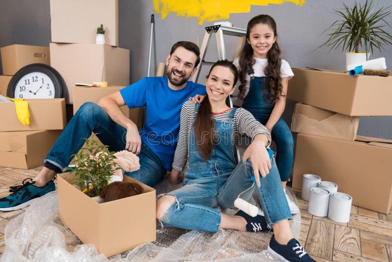 Glückliche junge Familie baut Pappschachteln ab und macht Heimwerken stockfotografie