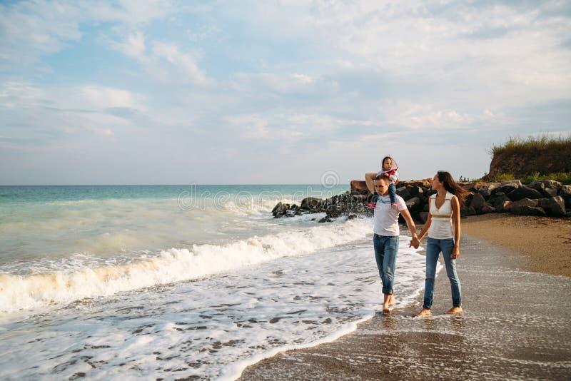 Glückliche junge Familie in den weißen T-Shirts und in den Blue Jeans mit einer kleinen Tochter im blauen Kleid gehend entlang di lizenzfreies stockbild