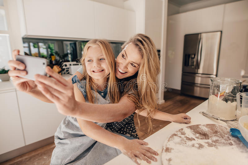 Glückliche junge Familie des Nehmens von selfie in der Küche stockfotos