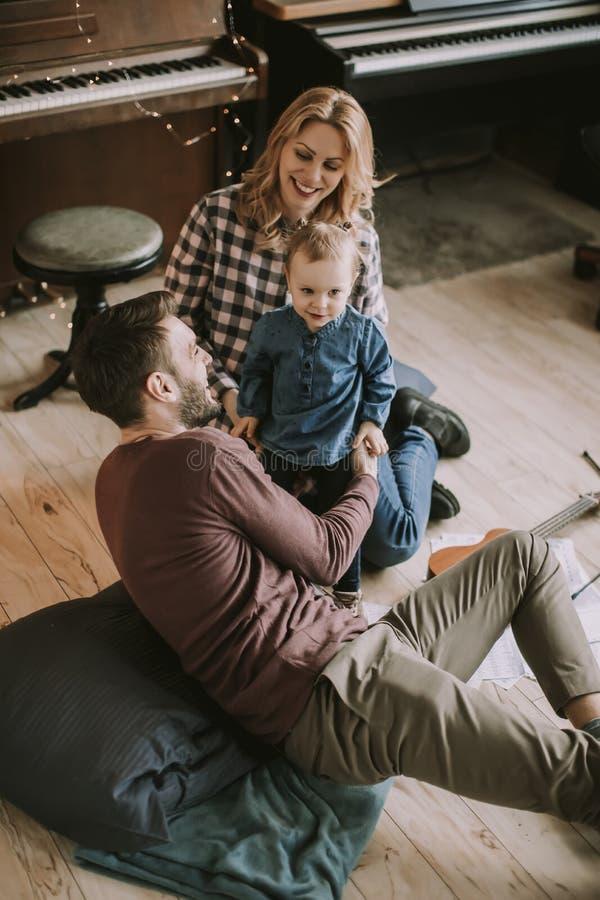 Glückliche junge Familie, die auf dem Boden spielt lizenzfreie stockfotos