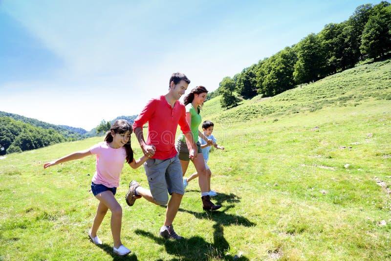 Glückliche junge Familie, die das Laufen in Naturlandschaft genießt stockfotos