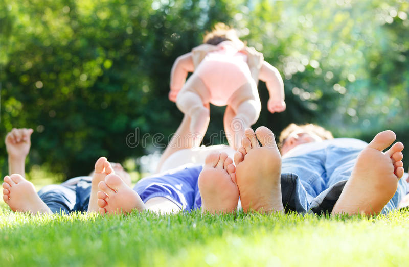 Glückliche junge Familie, die draußen auf grünem Gras liegt stockbild