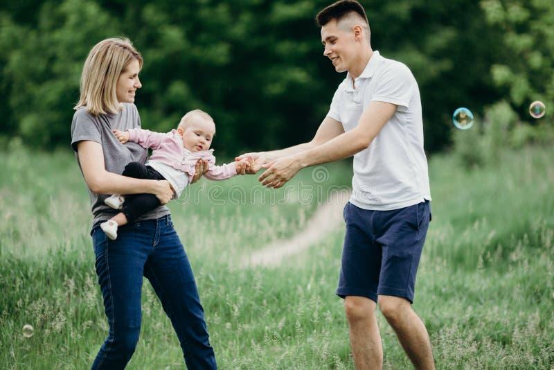 Glückliche junge Familie, die draußen spielt stockfoto