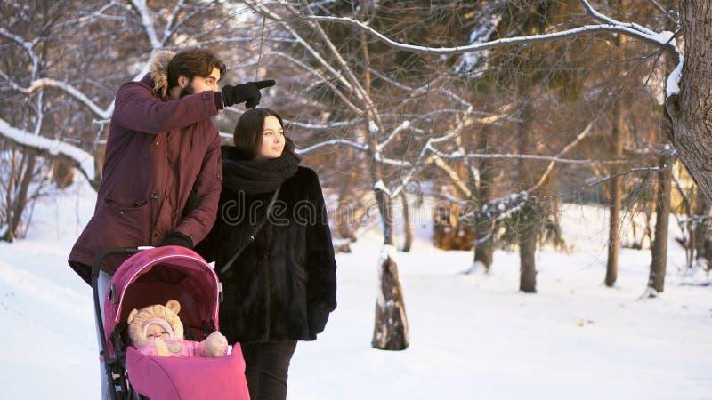 Glückliche, junge Familie, die in einen Winterpark gehen, Mutter, Vati und Baby im rosa Spaziergänger Mann, der den Finger und di stockbilder