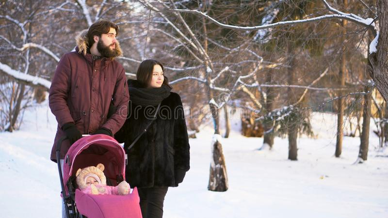 Glückliche, junge Familie, die in einen Winterpark gehen, Mutter, Vati und Baby im rosa Spaziergänger Mann, der den Finger und di lizenzfreie stockbilder