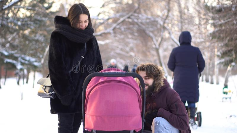 Glückliche, junge Familie, die in einen Winterpark gehen, Mutter, Vati und Baby im Spaziergänger Lächelnde Eltern, die über rosa  stockfotos