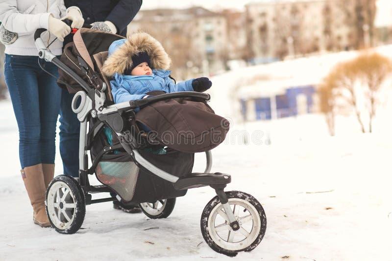 Glückliche junge Familie, die in einen Winterpark, -mutter, -vati und -sohn im Spaziergänger geht lizenzfreie stockbilder
