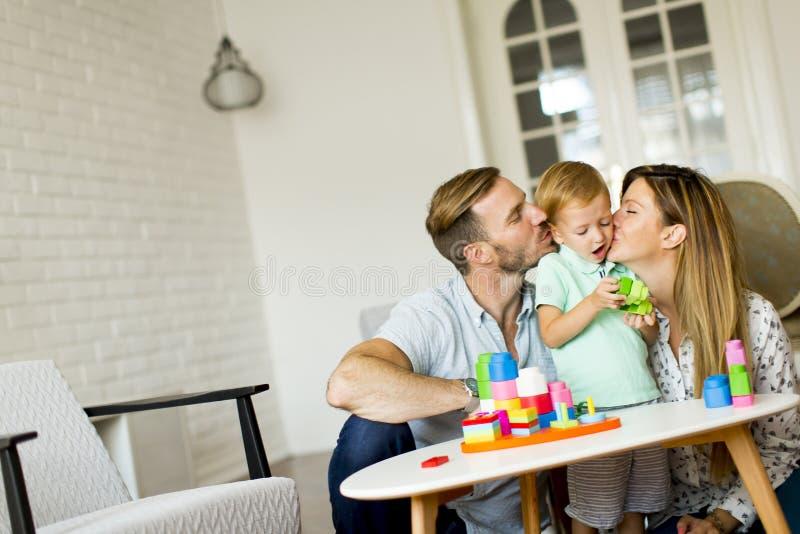 Glückliche junge Familie, die im Raum spielt lizenzfreie stockfotografie