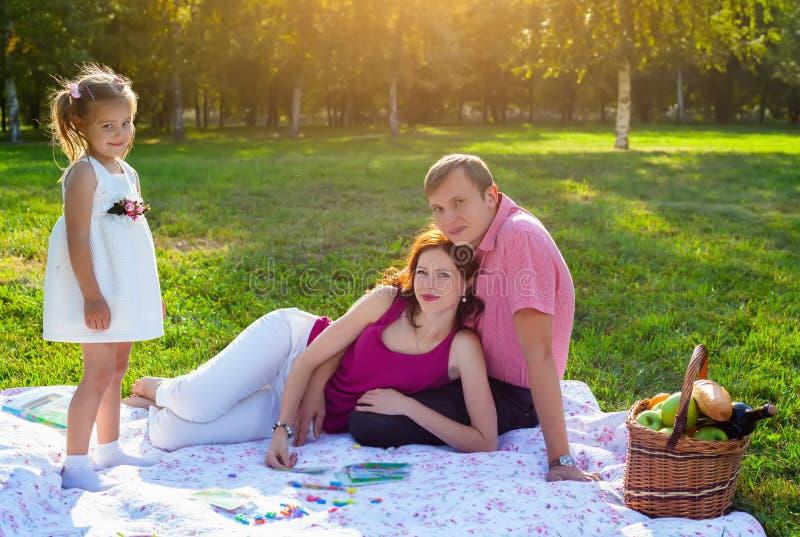 Glückliche junge Familie, die Picknick an der Wiese hat lizenzfreies stockbild