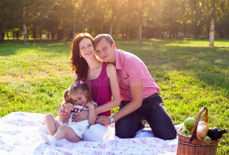 Glückliche junge Familie, die Picknick an der Wiese hat stockbild