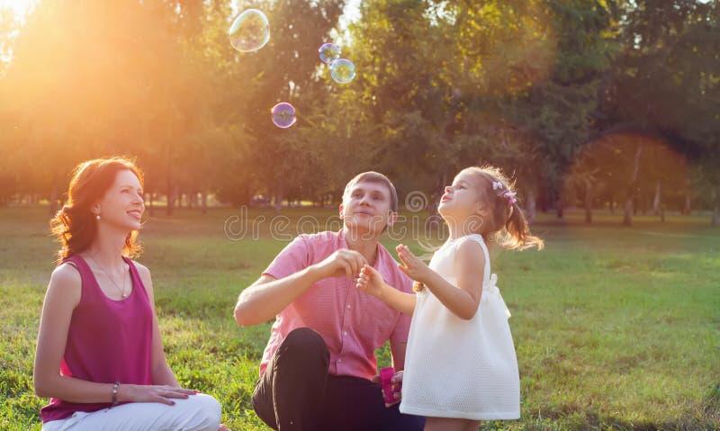 Glückliche junge Familie, die Picknick an der Wiese hat lizenzfreies stockfoto