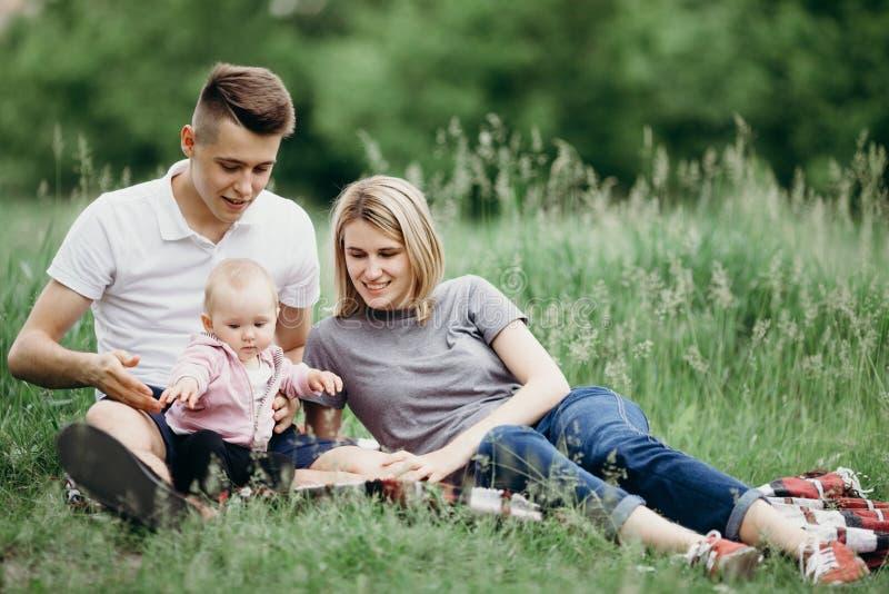 Glückliche junge Familie, die zusammen in der Natur stillsteht stockfotos