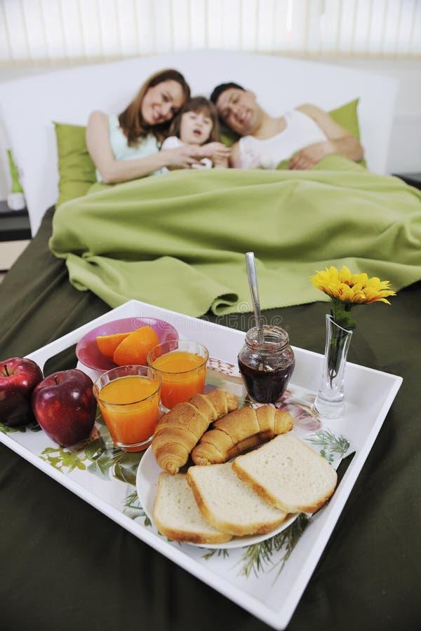 Glückliche junge Familie essen Frühstück im Bett lizenzfreies stockfoto
