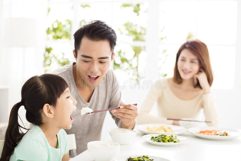 Glückliche junge Familie genießen ihr Abendessen lizenzfreie stockfotografie