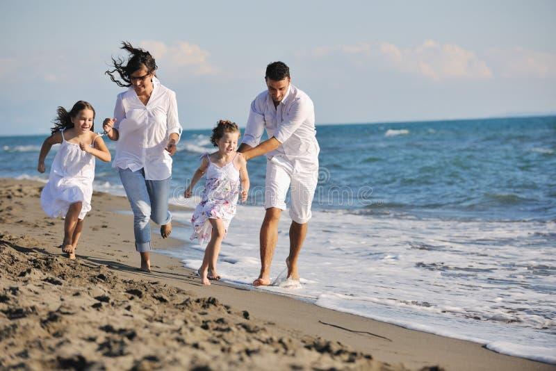 Glückliche junge Familie haben Spaß auf Strand lizenzfreies stockfoto