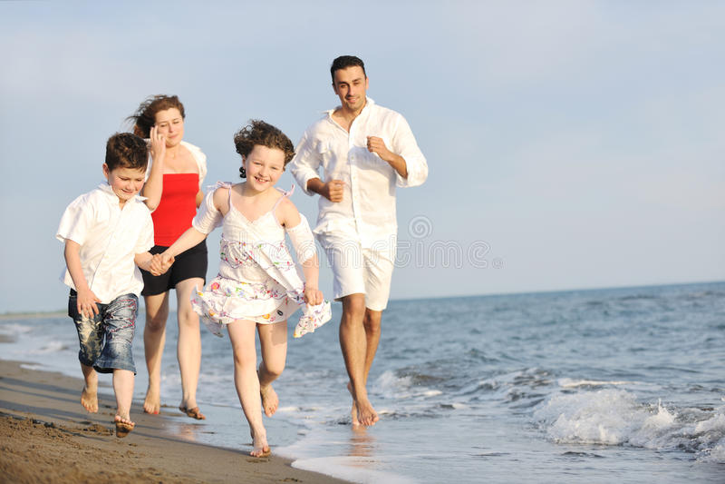 Glückliche junge Familie haben Spaß auf Strand stockfotos