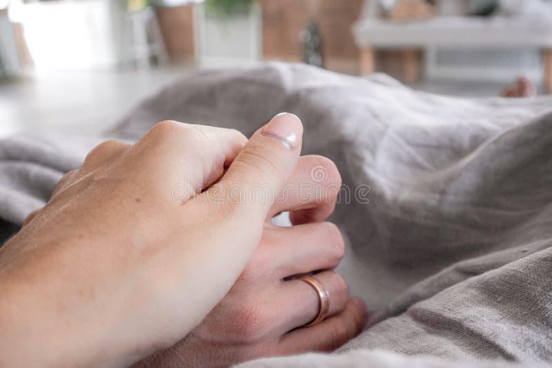 Glückliche junge Familie liegt im Bett unter Abdeckung früh morgens, Händchenhalten und wünscht guten Morgen lizenzfreies stockfoto