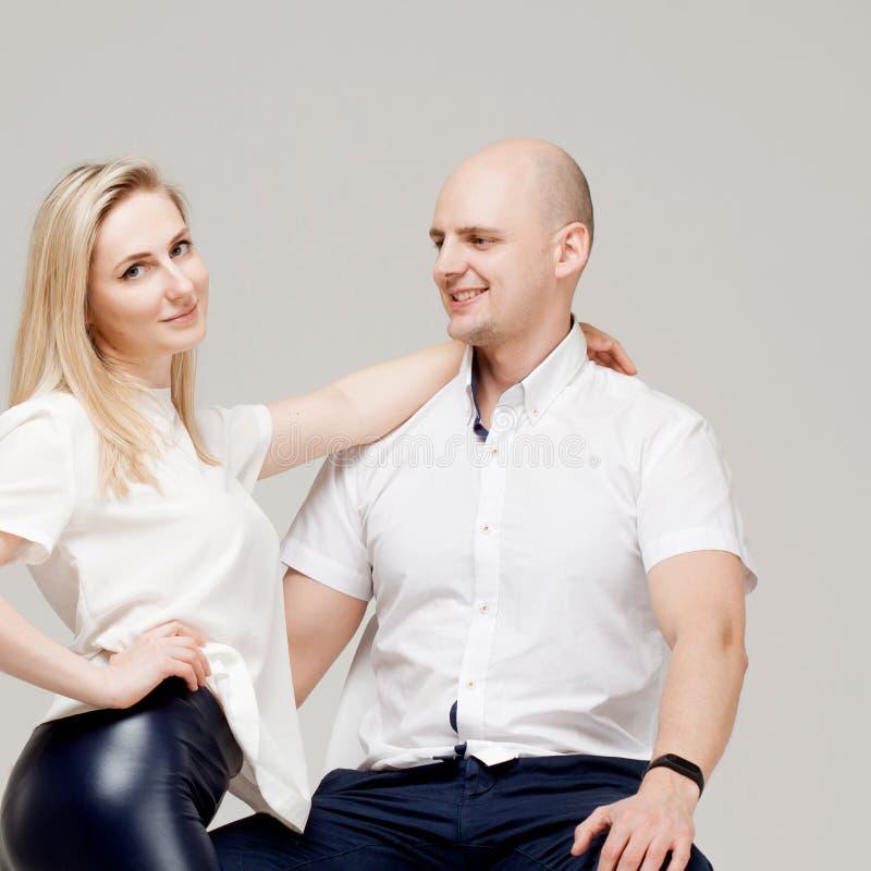 Glückliche junge Familie, Mann und eine Frauenumarmung, stilvolles Porträt stockfotografie