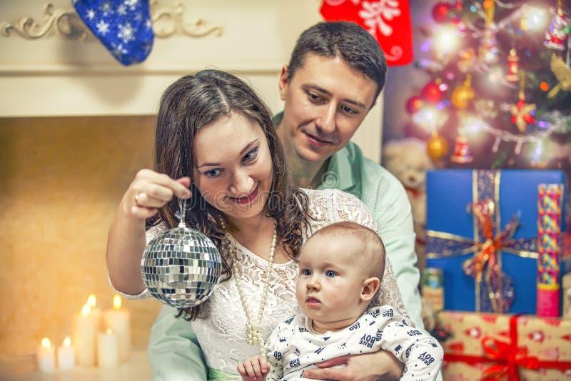 Glückliche junge Familie mit einem Kind nahe dem Weihnachtsbaum stockfotos