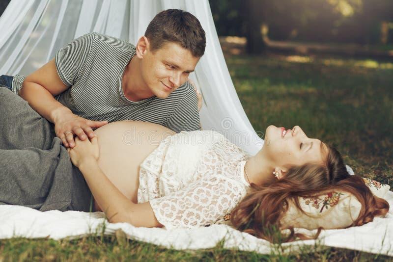 Glückliche junge Familie, relazing im sonnigen Park, glückliches Ehemann holdin stockfoto