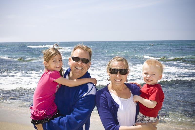 Glückliche junge Familie am Strand lizenzfreies stockfoto