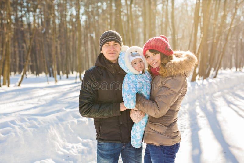 Glückliche junge Familie, welche die Zeit im Freien im Winter verbringt lizenzfreie stockfotos