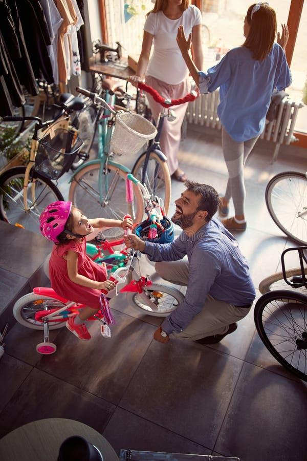 Gl?ckliche junge Familie zu kaufendem neuem Fahrrad in der Draufsicht des Speichers stockbild