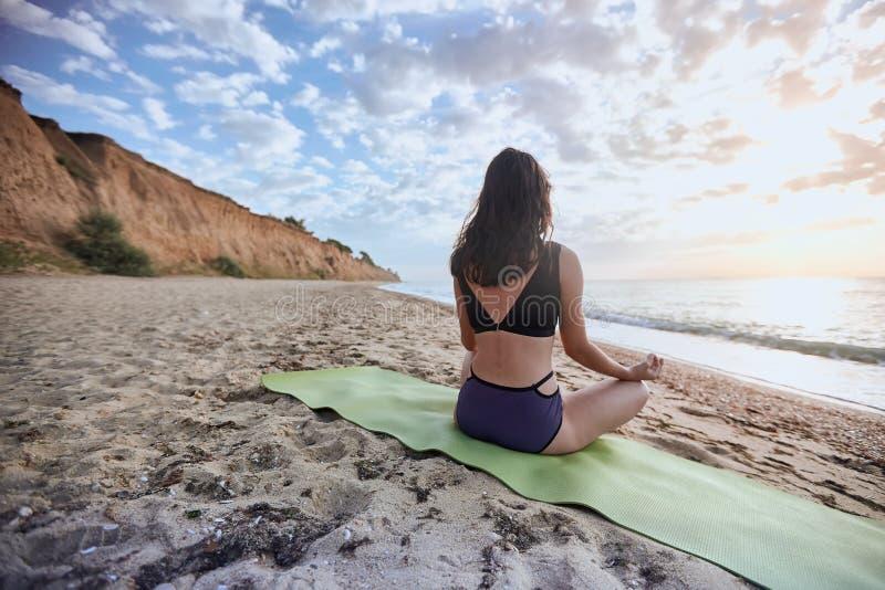 Glückliche junge Frau übt Yoga und meditiert im Lotussitz auf dem Strand lizenzfreies stockbild