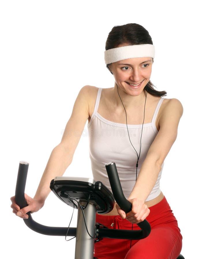 Glückliche junge Frau auf einem Trainingsfahrrad stockbild