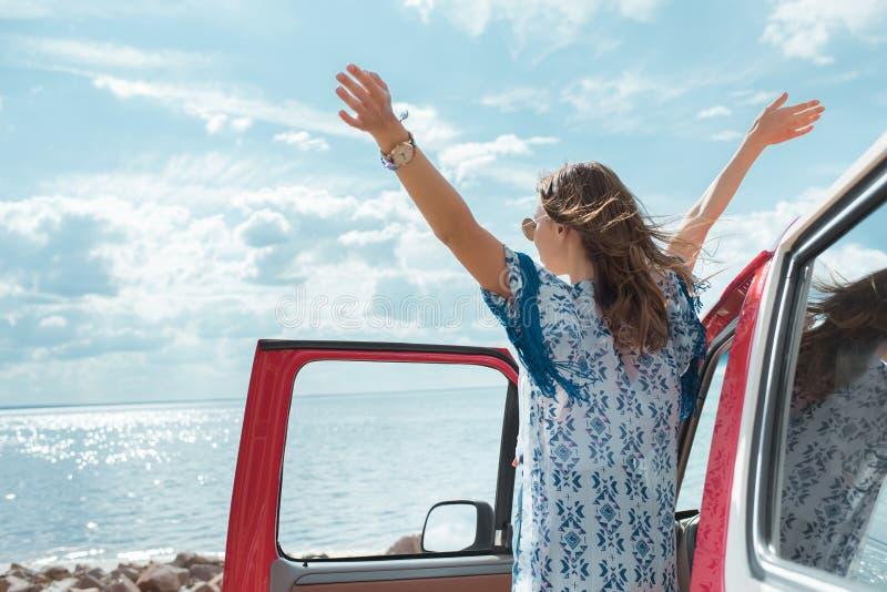 glückliche junge Frau beim Autoschauen stockbild