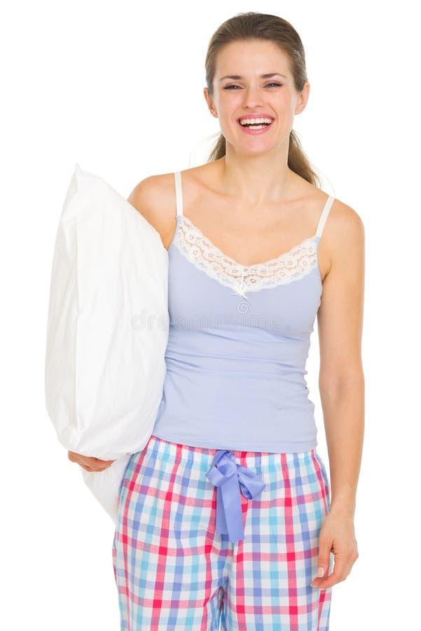 Glückliche junge Frau in den Pyjamas, die Kissen anhalten stockfotos