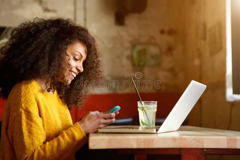 Glückliche junge Frau in der Kaffeestube unter Verwendung des Handys stockbild