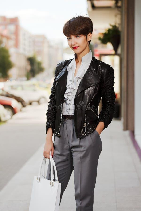 Glückliche junge Frau in der Lederjacke stockbilder