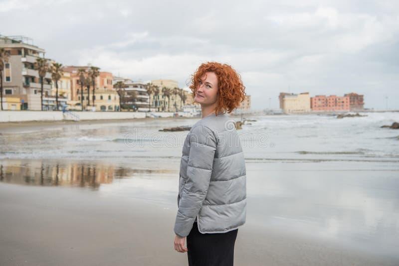 glückliche junge Frau in der Pufferjacke auf Küste lizenzfreie stockfotografie