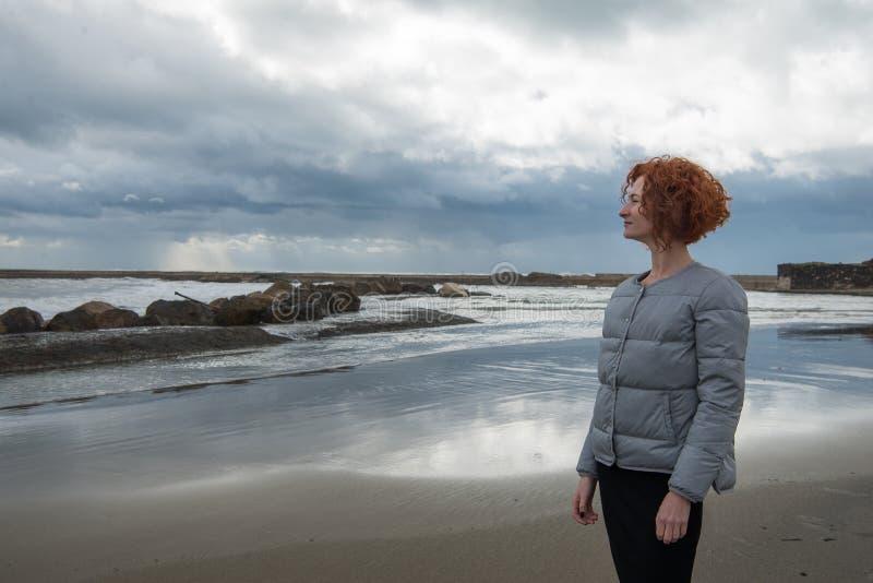 glückliche junge Frau in der Pufferjacke auf Küste am bewölkten Tag lizenzfreie stockbilder