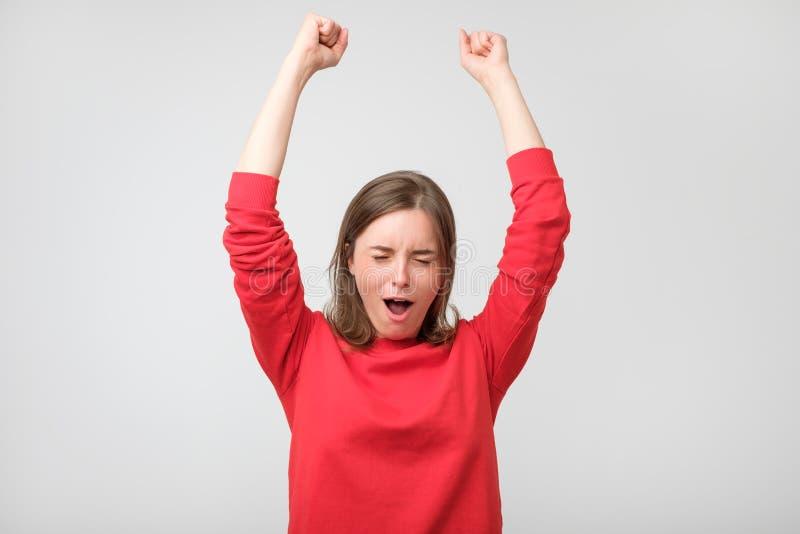 Glückliche junge Frau in der roten Abnutzung Augen gestikulierend und geschlossen halten stockfotos
