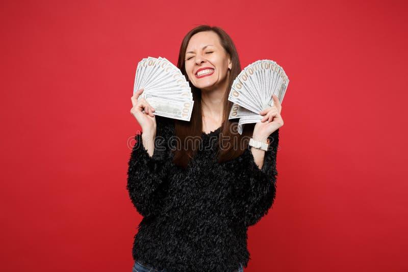 Glückliche junge Frau in der schwarzen Pelzstrickjacke mit den geschlossenen Augen, die Fan des Geldes in den Dollarbanknoten, Ba lizenzfreie stockfotografie