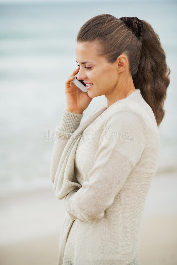Glückliche junge Frau in der Strickjacke an Unterhaltungshandy des Strandes stockfotografie