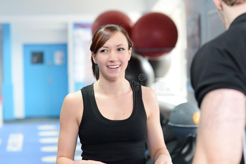 Glückliche junge Frau in der Turnhalle mit persönlichem Trainer lizenzfreies stockfoto