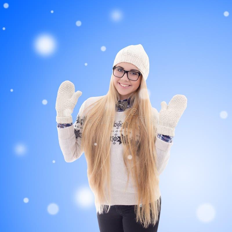 Glückliche junge Frau in der warmen Kleidung über blauem Winterhintergrund stockbild