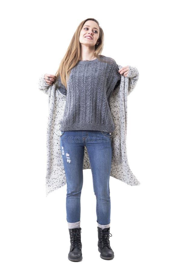Glückliche junge Frau in der warmen Winterkleidung, die gestrickte lange Wolljacke weg lächelnd und schauend entfernt stockfoto