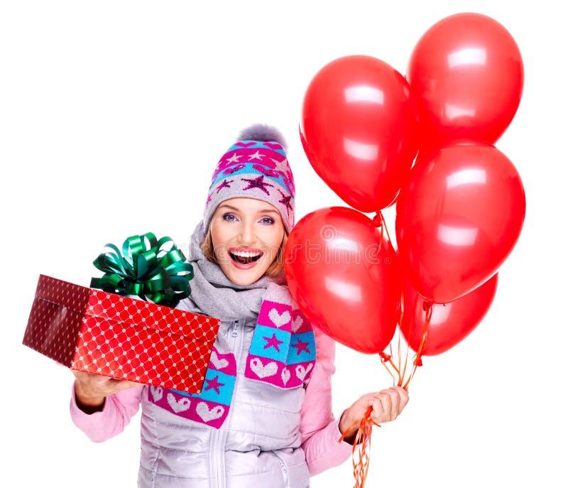 Glückliche junge Frau des Spaßes mit roter Geschenkbox und Ballonen stockfotografie