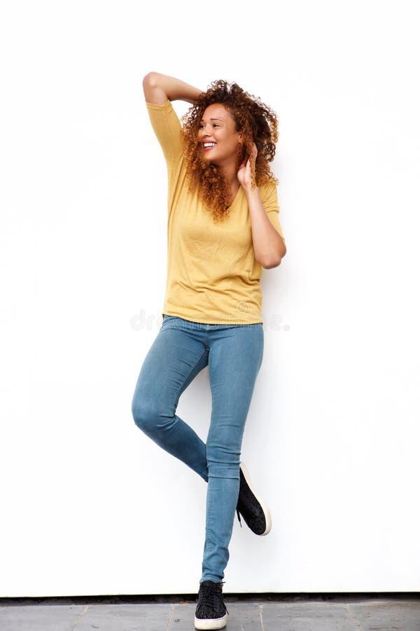 Glückliche junge Frau des vollen Körpers mit den Händen im gelockten Haar gegen weiße Wand lizenzfreie stockfotografie