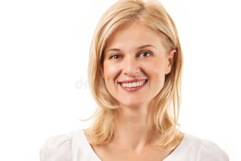Glückliche junge Frau, die über Weiß lächelt lizenzfreie stockfotografie