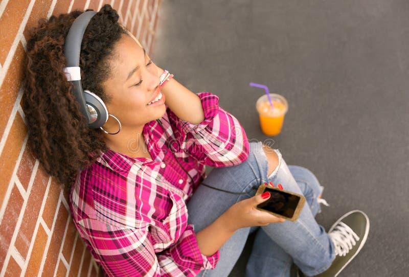 Glückliche junge Frau, die auf dem Boden hört Musik sitzt stockfotos