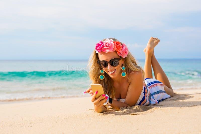 Glückliche junge Frau, die auf dem Strand im Sand liegt und Handy verwendet stockbilder