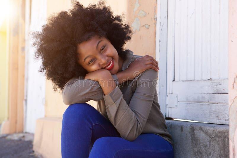 Glückliche junge Frau, die auf den Schritten lehnen Kopf auf Armen sitzt stockbilder