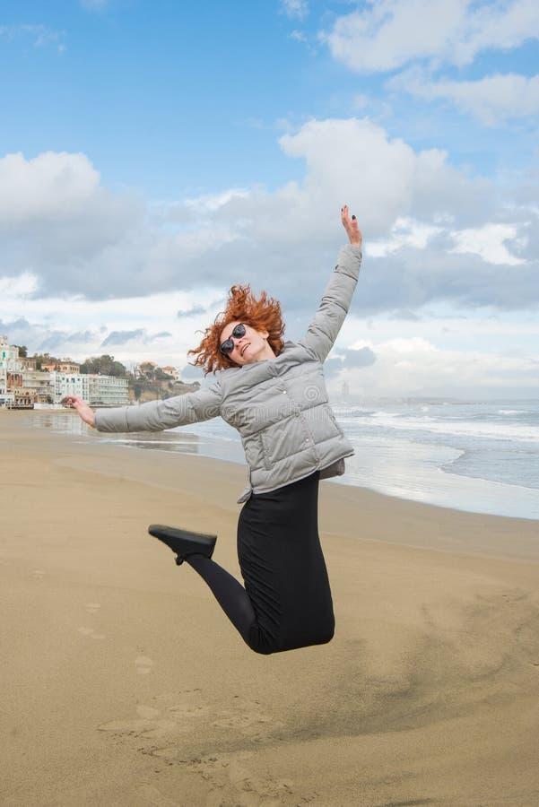 glückliche junge Frau, die auf Küste am bewölkten Tag springt stockbilder